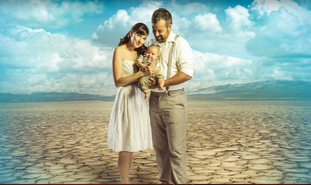 a couple with a new Baby, standing in a desert