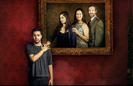 a young man in front of a family portrait that is missing him