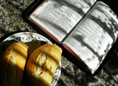 Bible next to a plate with two loaves of bread