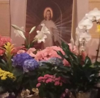 Divine Mercy painting behind flowers at the altar