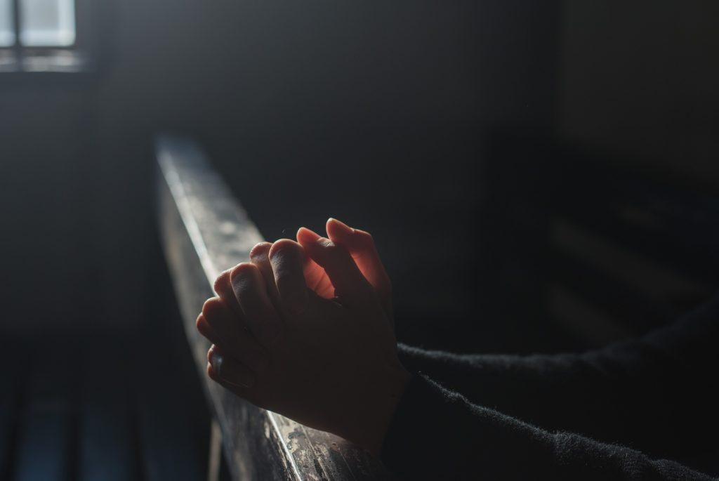 Praying hands in a darkened church